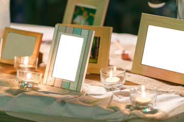 A Table in Wedding party decoration with candle and photo frame in evening time.