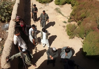 Afghan policemen hold their weapons near a house in a village