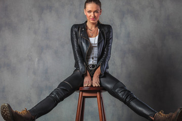 woman in leather clothes and boots stretching her legs