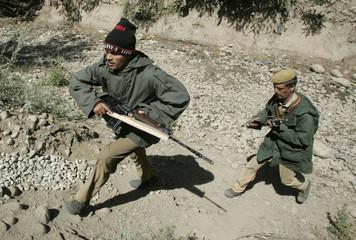 Indian policemen run during a gun battle in Tujan