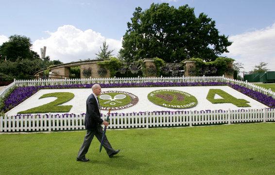 MAN WALKS PAST FLOWER GARDEN WITH WIMBLEDON LOGO.