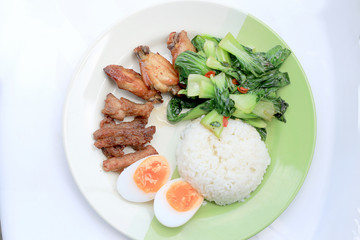 stir fried vegetables, Hard-boiled egg, Fried pork and Fried chicken wings with thai jasmine rice on dish. Thai food.