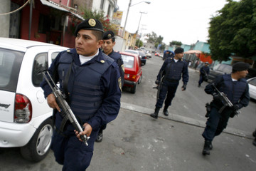 Policemen stand guard during an anti-narcotics operation in the Venustiano Carranza district in Mexico City