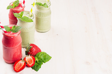 Green and red fruit smoothie in glass jars with straw, mint leaves, strawberry and apples. White wooden board background, copy space.