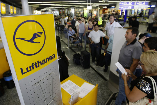 Passengers queue up in front of the ticket desks of German airline Lufthansa in the departure hall of Frankfurt airport