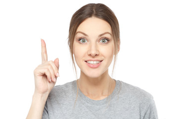Photo of energetic nice smiling lady wearing grey top isolated on white background pointing her finger in eureka sign, having great innovative idea, understanding or solution she has just got.
