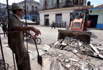 Cuban worker gathering rubble with help of bulldozer after Hurricane Charley.