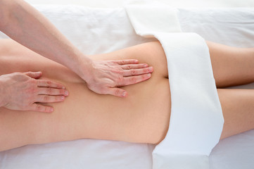 Top view of a professional masseuse doing back massage to female client