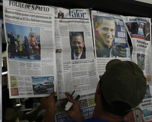 A vendor displays Brazilian morning newspapers, with the front pages showing U.S. President Obama's inauguration, in Brasilia