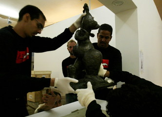 Workers install Picasso's 'Baigneuse' bronze sculpture at the Oca in Ibirapuera Park during final pr..