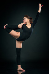 graceful girl gymnast standing stretching in One leg in splits against dark background