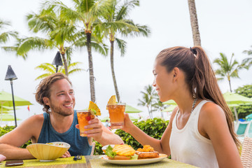 Fotobehang - Couple eating at hotel restaurant on Hawaii travel vacation beach drinking hawaiian drink mai tai. Happy people toasting cheers with cocktails. Summer holidays at resort.