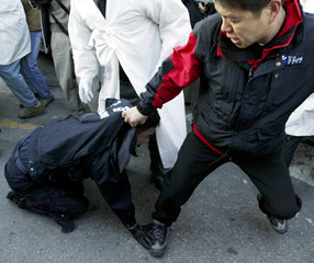 WORKER HOLDS A RIOT POLICEMAN AT A PROTEST IN SEOUL.