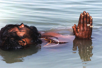 A Hindu holy man floats in the river Hooghly in the eastern Indian city of Calcutta January 9. Monks..