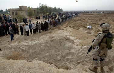U.S. marines stand on guard near Iraqis queuing to vote in the national polls in a polling precinct in ...