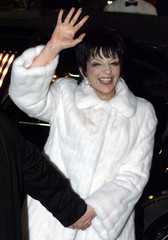 Singer Liza Minnelli waves to fans as she arrives for the reception following her marriage to produc..