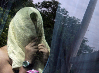 A FARC rebel with his face covered arrives at a farm in Chicoral