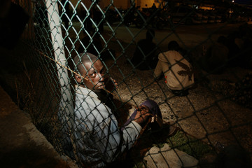 Would-be immigrants sit after been detained in Spain's North African enclave of Melilla
