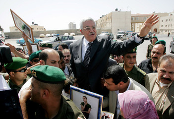 Palestinian President Mahmoud Abbas greets protesters outside his headquarters in Ramallah.