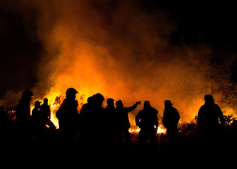 Villagers and firefighters look at a forest fire in the outskirts of Viana do Castelo city in ...