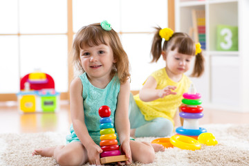 Children playing together. Educational toys for preschool and kindergarten kids. Little girls build pyramid toys at home or daycare.