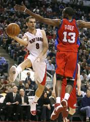 Toronto Raptors guard Jose Calderon passes the ball past Los Angeles Clippers guard Quinton Ross in Toronto