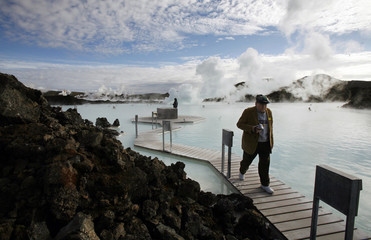 A tourists walks near the geothermal hot springs at Iceland's Blue Lagoon near Grindavik