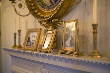 Close Up Isolated View of a Staged All White Fireplace Mantel. White Walls, Antique Gold Candlesticks/Candles Family Photos in Gold Frames, Partial View Gold Mirror (HDR Image)