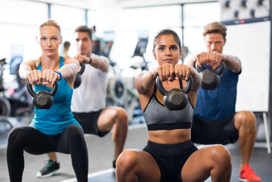 People with kettlebells squatting