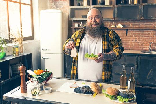 Cheerful thick guy enjoying burger preparation