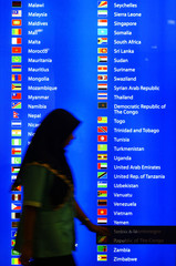 MALAYSIAN WOMAN WALKS IN FRONT OF DISPLAY OF MEMBER COUNTRIES OF THENON-ALIGNED MOVEMENT IN KUALA ...