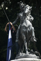 A supporter of Honduras' ousted President Manuel Zelaya hangs a Honduras flag on the hand of the statue of Francisco Morazan in Tegucigalpa