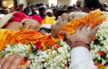 A man stretches out his hand to pay his last respects to former Bollywood icon and Indian sports ...