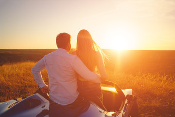 Happiness couple stay in the new sport car hugging and kissing at sunset