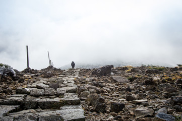 One person hiking to the peak of Mount Kumanodake - Stock image