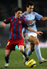 Barcelonas player Leo Messi struggles for the ball with Celtas Borja Oubina during their Spanish League soccer match in Barcelona