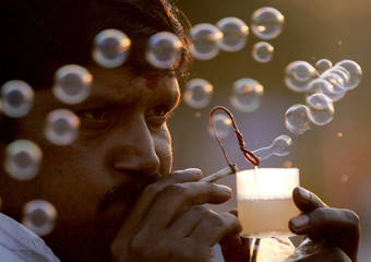 An Indian vendor makes soap bubbles from an improvised pipe in New Delhi March 11, 2005. More than 4..