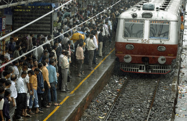 Commuters wait as a train approaches a railway station in Mumbai