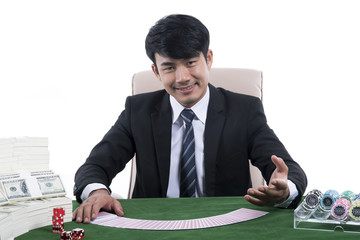 The Young dealer in black suit with gesture inviting and gambling devices on green table