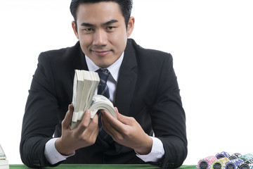 Portrait handsome man in black suit holding piles of dollars and stack chips nearby