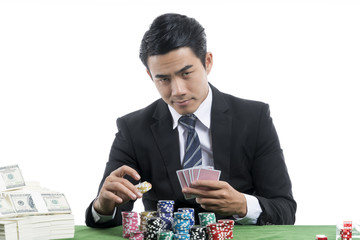 The young gambler is putting bets into the piles of chips