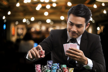 Portrait handsome man in black suit is putting stack of chips and holding poker card