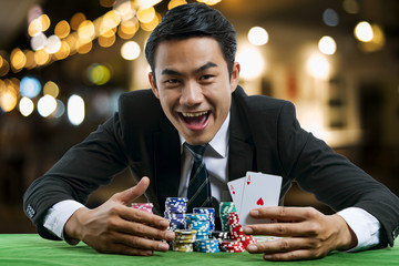 The poker gambler showing a pair of red aces and hold bet a large stack with arms