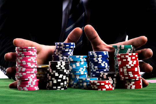 A poker Player hands pushing in all his chips to betting