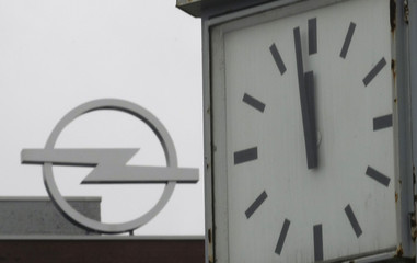 A clock is pictured in front of the logo of the Opel plant in Bochum