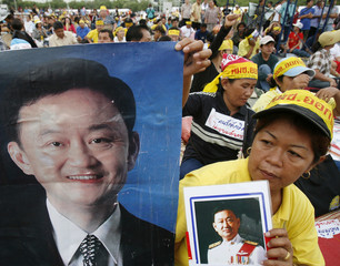 A demonstrator holds pictures of ousted Prime Minister Thaksin during an anti-coup rally near Bangkok's Grand Palace