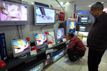CUSTOMERS LOOK AT LOCALLY MADE TELEVISIONS IN SHANGHAI.