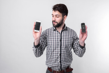 Bearded man isolated on a light background holding a modern smartphone and old cell phone with buttons