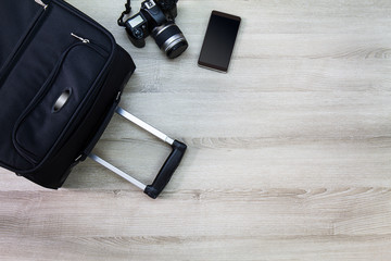 Travelling bag,camera and smartphone on wooden background
