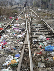 Woman walks across railway tracks covered with rubbish at a slum in Hefei